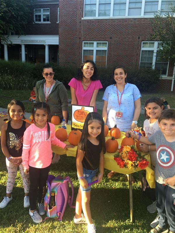 Children and adults pose in front of a table full of pumpkins.