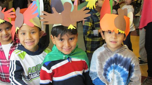 Children smiling with paper turkey hats on their heads.