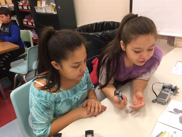 Two girls working together while building a car out of Legos.