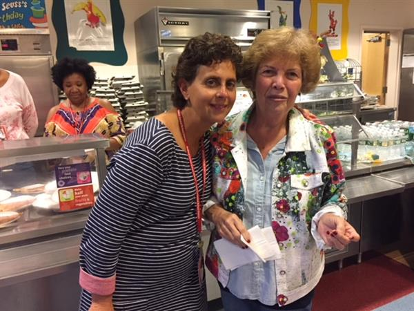 Two MKES staff members smiling for the camera in the cafeteria.