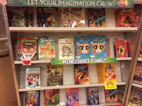 Several children's books are on book fair shelving units.