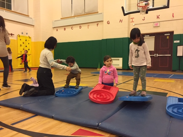 Children on a gymnastics mat balancing.