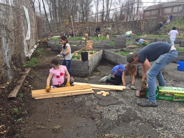 Children and adults work in the school's community garden.