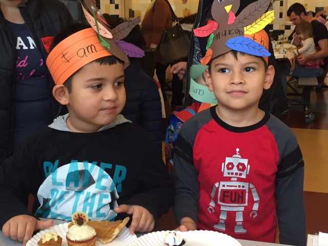 Children with turkey hats at table.