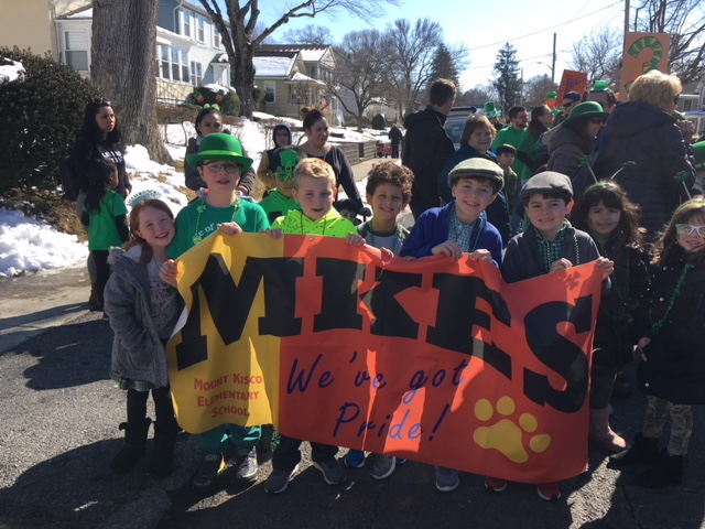 Children are gathered on the street behind an MKES banner.