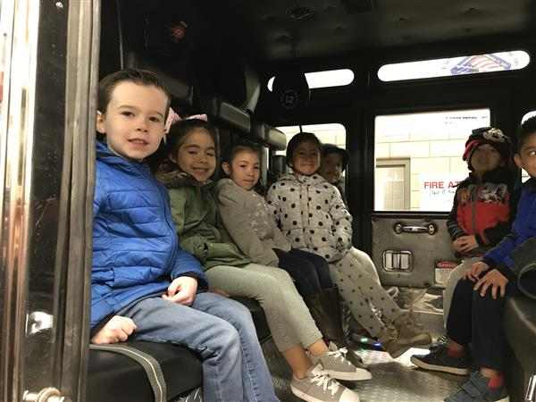 Children sitting in a fire truck.