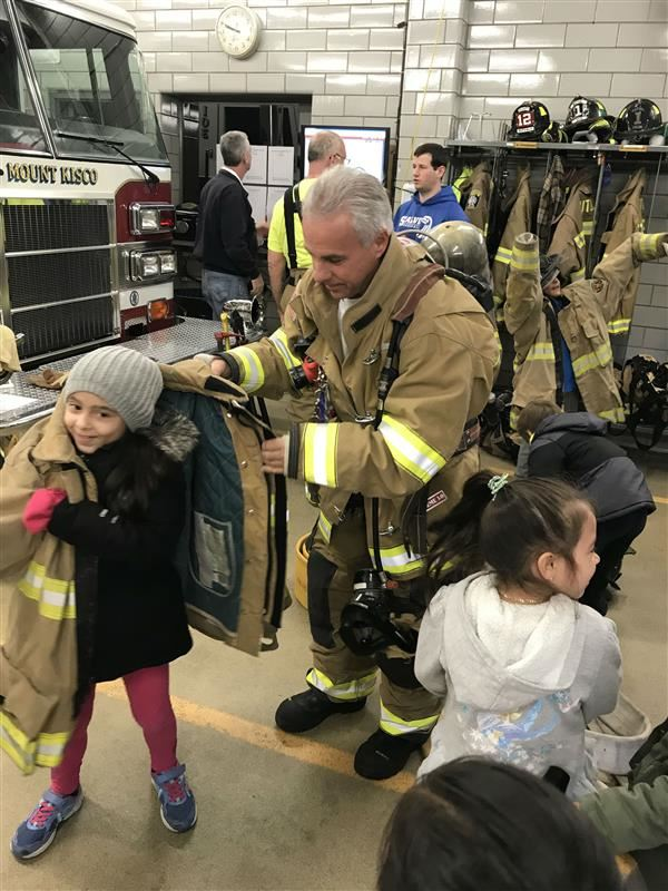 An MKES 1st Grader tries on a fireman's jacket.
