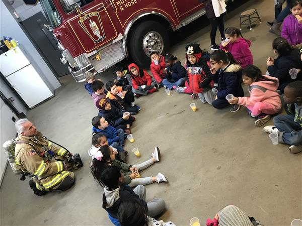 MKES first graders sit in a circle inside the firehouse.