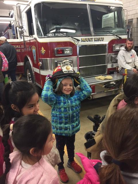 A little girl smiles while wearing a firefighter's helmet.