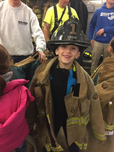 A little boy smiles while wearing a fire fighter's helmet.