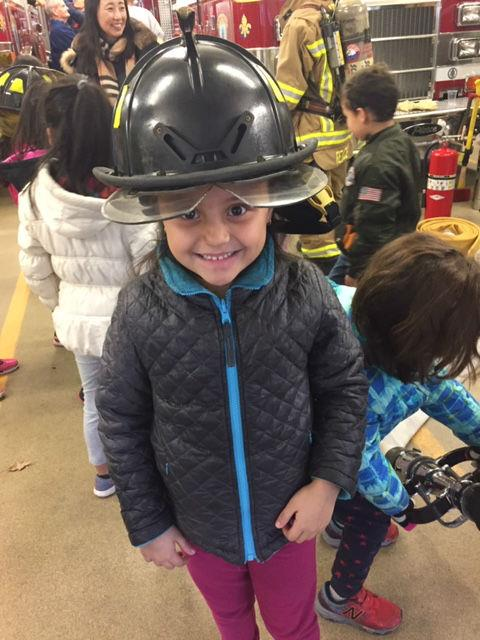 A little girl smiles while wearing a fire fighter's helmet.