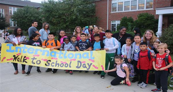 A group of children and staff celebrate International Walk to School Day with a banner.