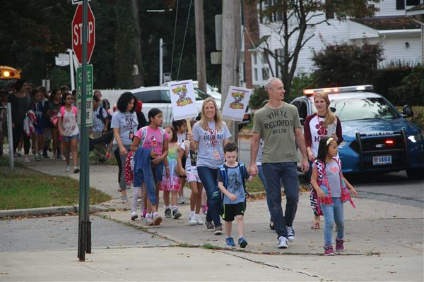 Children, their family members and staff walk to school.