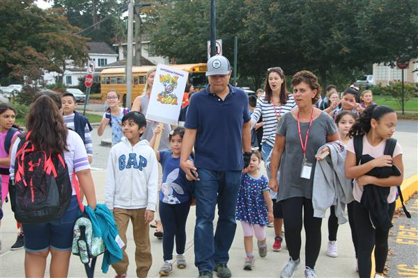 Children, their parents and staff walk together to school.
