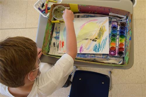student stands over desk, working on watercolor painting inside a cardboard tray
