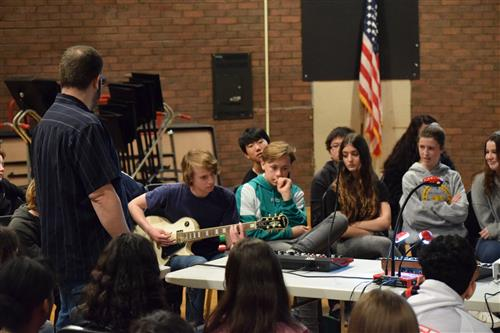 FLMS students participating in sound wave presentation - student playing guitar