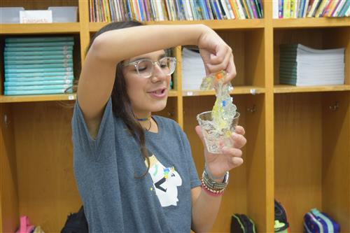student plays with slime cell model