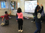 MKES students exercise while watching their PRES peers do the same on the smartboard