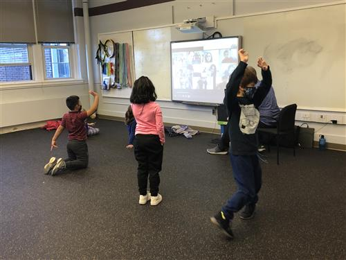 MKES students exercise while watching PRES peers on smartboard