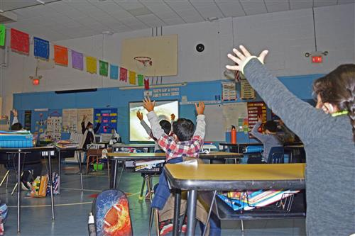 students and teacher raise their hands in the air