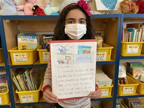 second grader holds up her book review in front of a wall filled with books