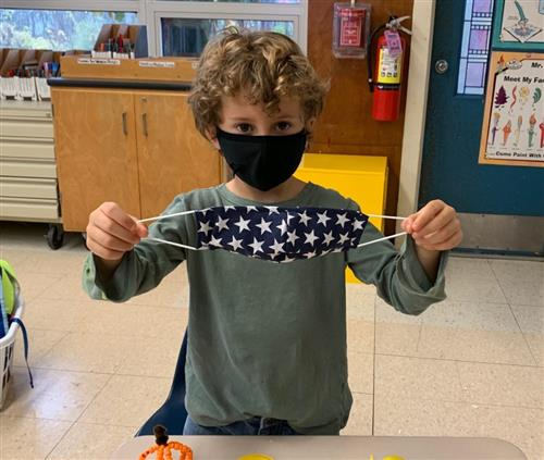 BVES student holds up starry mask made by FLMS student