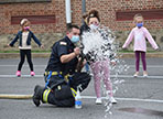 firefighter and student spray firehose